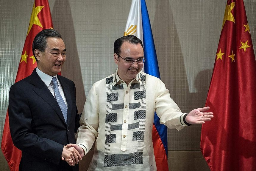 "Chinese Foreign Minister Wang Yi (far left) meeting his Philippine counterpart Alan Peter Cayetano in Manila yesterday. Mr Wang said joint development of natural resources in disputed waters ""is full of political wisdom""."