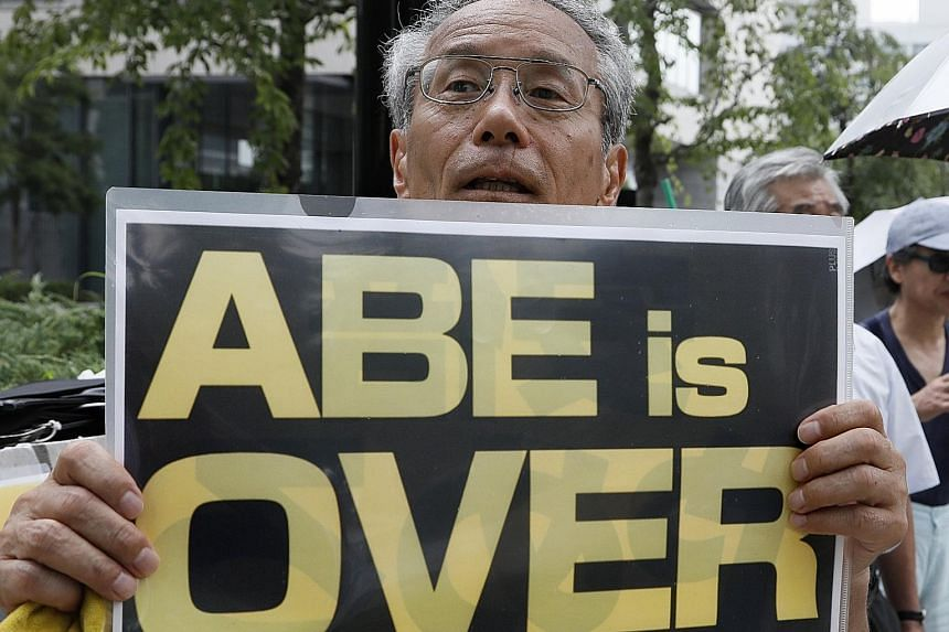 A demonstrator outside Parliament in Tokyo yesterday as Prime Minister Shinzo Abe tries to defend himself against accusations of cronyism during a special parliamentary session.