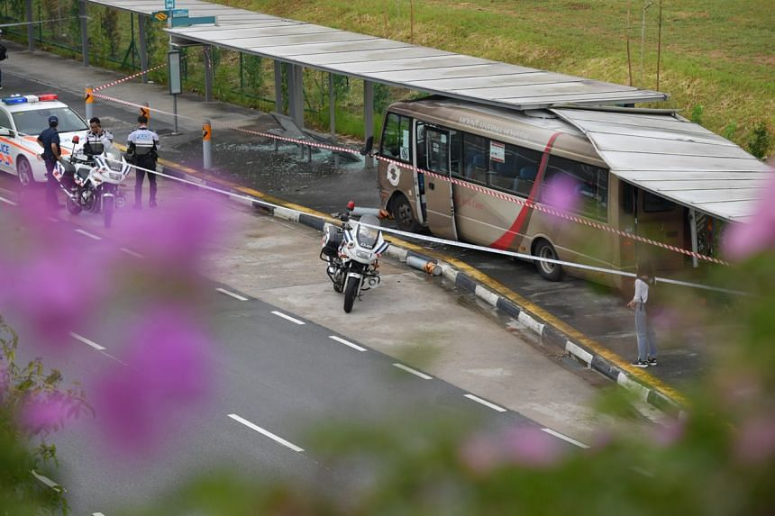 Police at the scene of the accident along Braddell Road on Wednesday (July 26). The badly damaged bus landed in the opposite direction of traffic, with debris strewn all over the pavement.