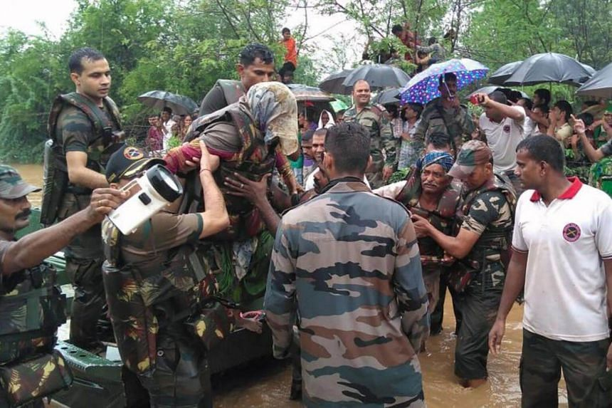 Indian rescue workers evacuating flood victims in Deesa municipality, which has been hit by severe flooding along the Banas River in western India.