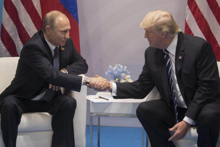 Russian President Vladimir Putin and US President Donald Trump shake hands at the G20 conference in Hamburg, Germany, July 7, 2017.
