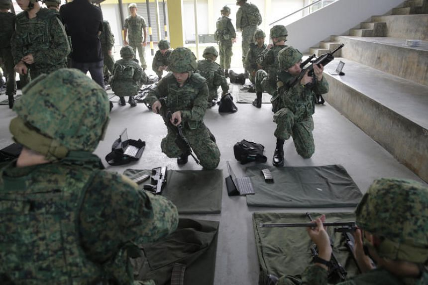 Recruits undergoing weapon handling practice with the SAR21 rifle in a training shed at the Singapore Armed Forces Basic Military Training Centre in Pulau Tekong.