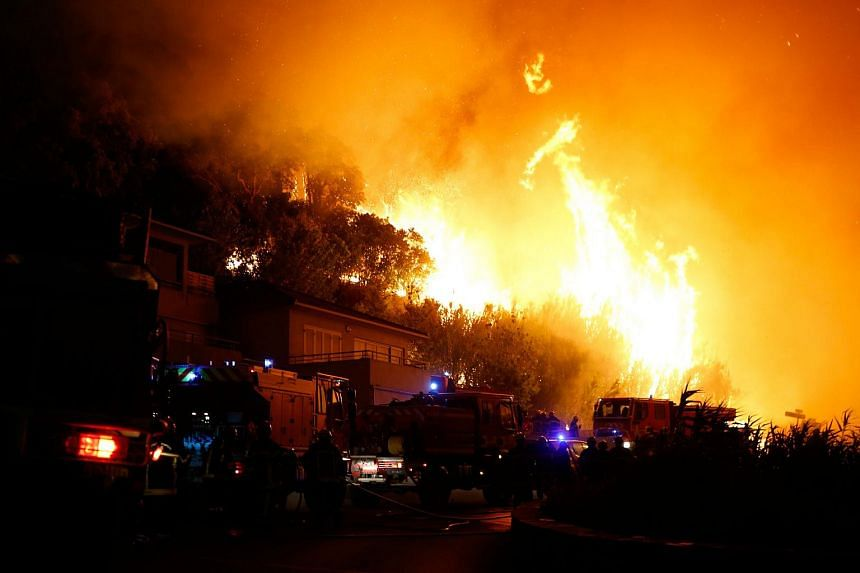 Firefighters work to put out a fire in Biguglia, on the French Mediterranean island of Corsica, on July 24, 2017.