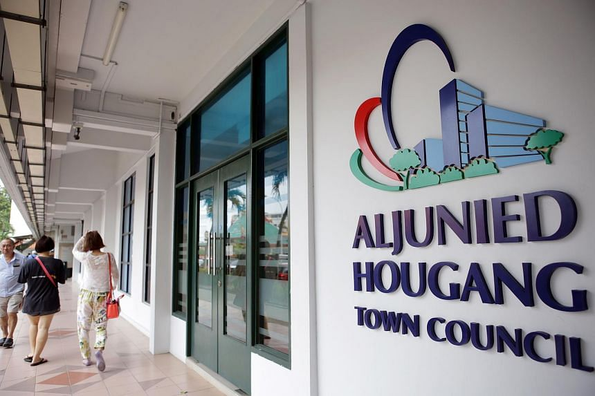 Residents walk past the entrance of the Workers' Party-run Aljunied-Hougang Town Council (AHTC).