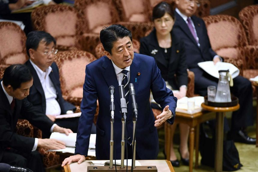 Japan's Prime Minister Shinzo Abe (C) answers questions during a budget dommittee meeting in the Upper House at parliament in Tokyo on July 25, 2017, as he and other relevant ministers were expected to face more questioning over issues over a suspect