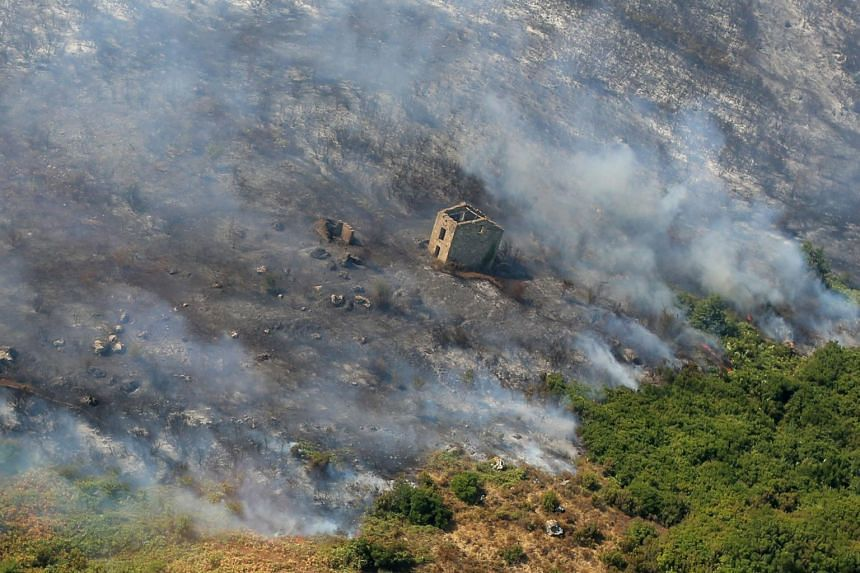 An aerial view taken shows the fire devastated landscape in Biguglia, on the French Mediterranean island of Corsica, on July 25, 2017.