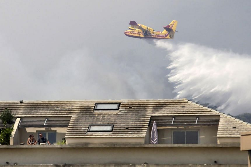 People stand outside on a balcony as a Canadair aircraft drops water over a fire behind the building in Ortale de Biguglia, near Biguglia, on the French Mediterranean island of Corsica, on July 25, 2017.