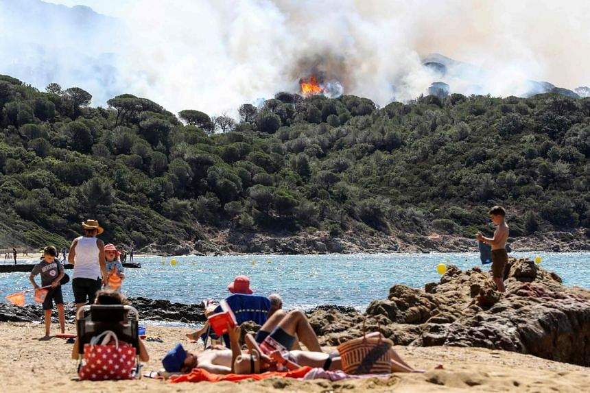 People enjoy the beach during a forest fire in La Croix-Valmer, near Saint-Tropez as firefighters keep on battling blazes across southern France, on July 25, 2017.