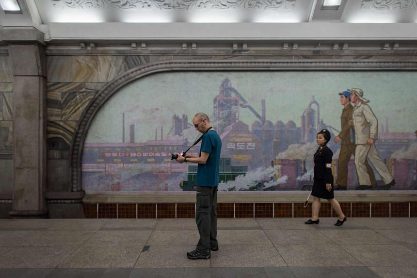A tourist takes a photo during a visit to a subway station in Pyongyang on July 23, 2017.