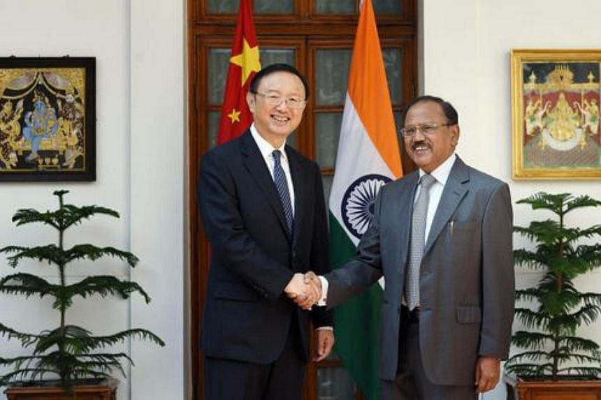 Chinese State Councilor Yang Jiechi (left) shake hands with Indian National Security Adviser Ajit Kumar Doval prior to a meeting in New Delhi, India, on March 23, 2015.