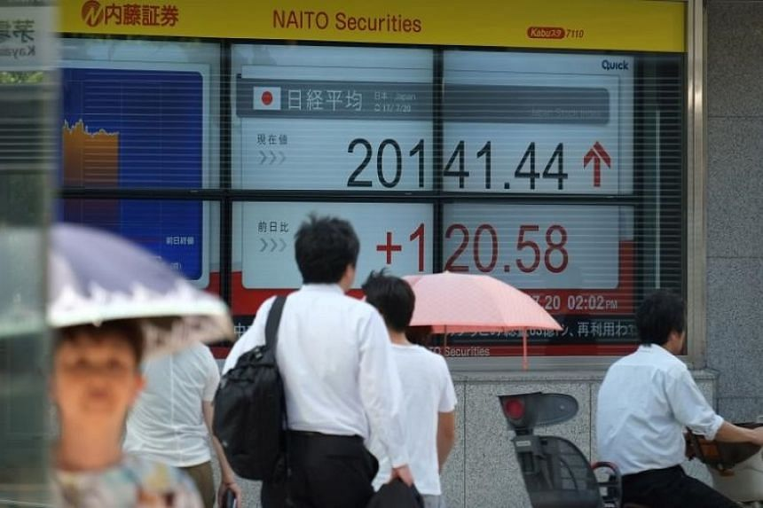 Pedestrians walk in front of a stock quotation board flashing the Nikkei 225 key index of the Tokyo Stock Exchange in Tokyo, Japan, on July 20, 2017.