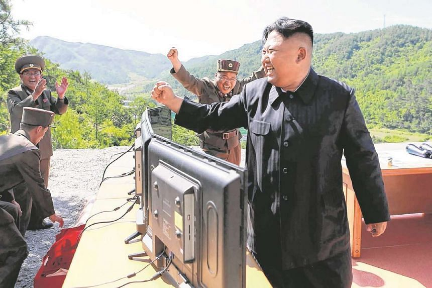 North Korean leader Kim Jong-Un (right) reacting after the test-fire of the intercontinental ballistic missile Hwasong-14 at an undisclosed location.