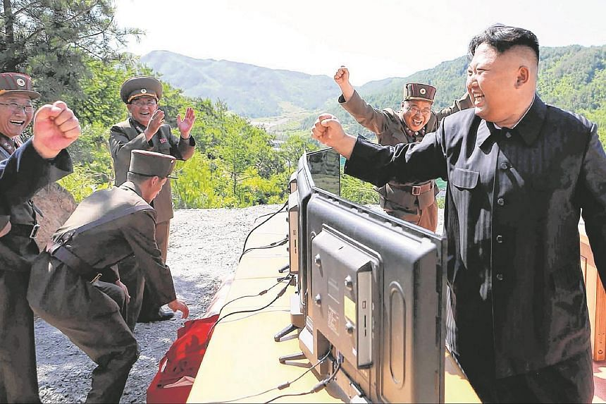 This picture taken and released on July 4, 2017, by North Korea's official Korean Central News Agency (KCNA) shows North Korean leader Kim Jong Un (right) reacting after the test-fire of the intercontinental ballistic missile Hwasong-14 at an undiscl