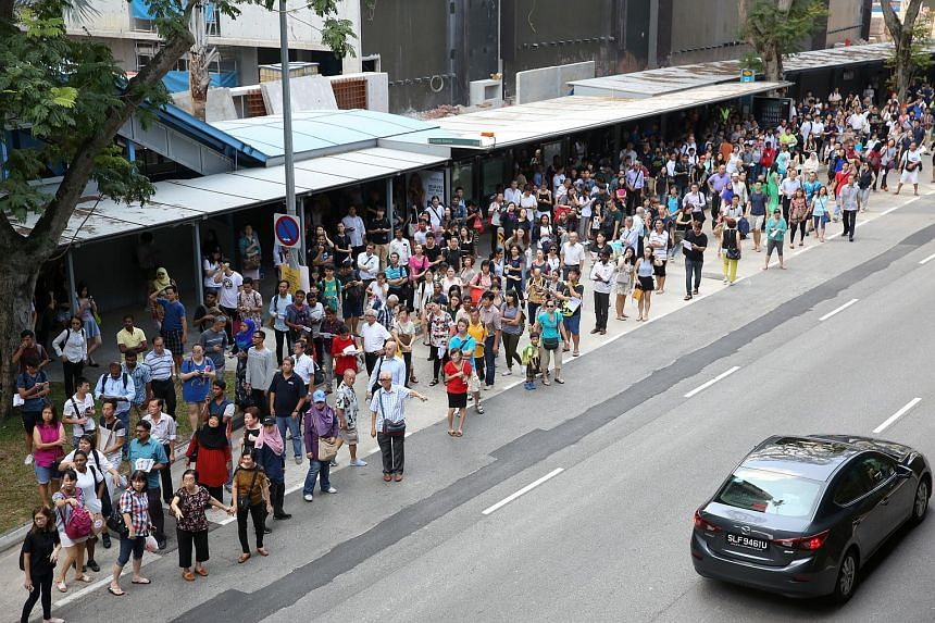 The crowd at the bus stop below Queenstown MRT after train service stopped on July 25, 2017.