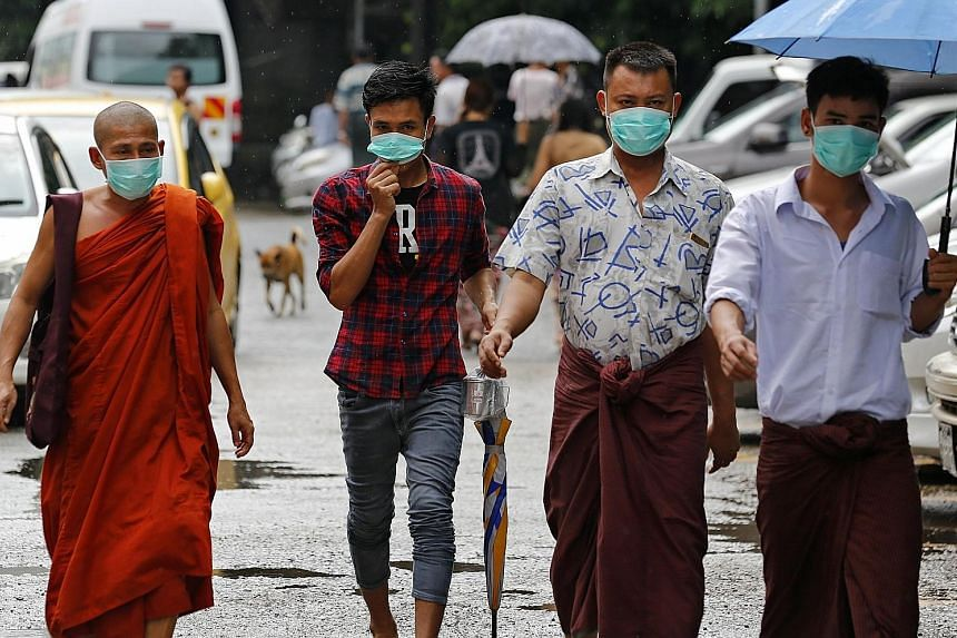 Passers-by don masks outside Yangon General Hospital in Yangon, Myanmar, yesterday, as reports confirm that at least four people in the country have died from the H1N1 flu virus. Over a dozen patients with the virus were also confirmed in various reg