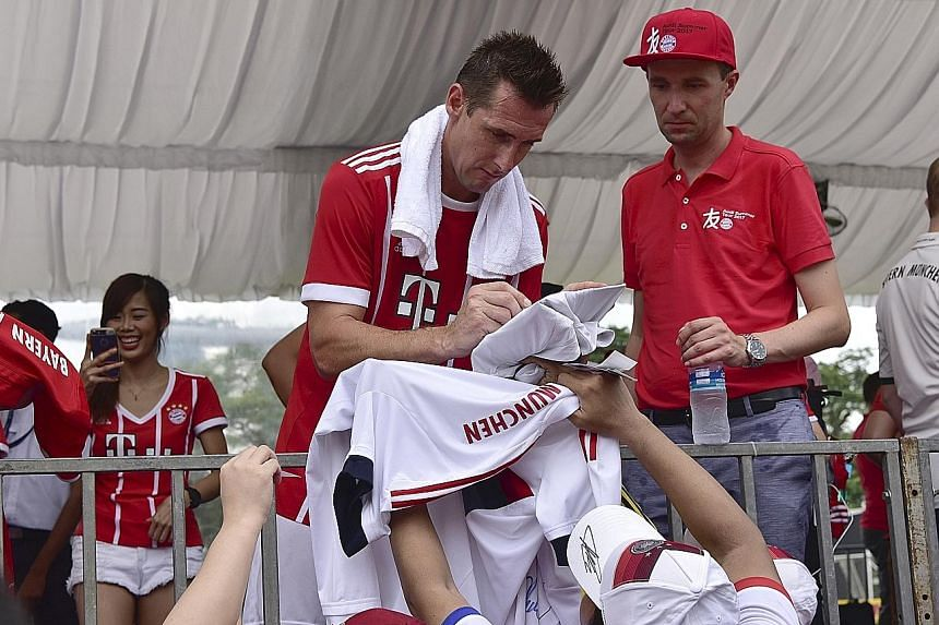 Former Bayern Munich striker Miroslav Klose, the all-time World Cup top scorer, signing autographs for fans during a Bayern Munich Fan Club tournament at the Padang yesterday. The event saw former Bayern players Giovane Elber, Hasan Salihamidzic and