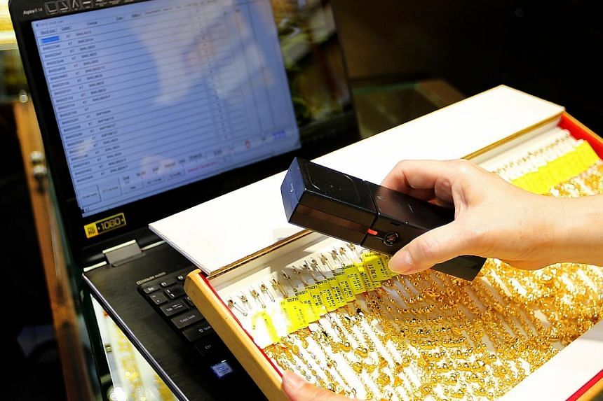 Ngee Soon Jewellery executive director Jan Ho, whose shop is one of the earliest adopters of the RFID technology. Above right: The system uses a scanner to process the jewellery pieces for stock-taking.