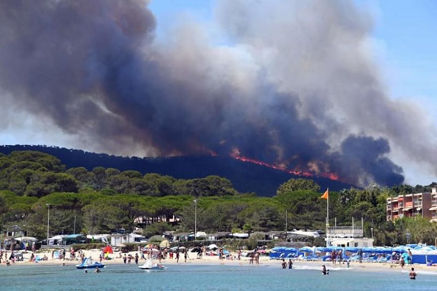 People on the beach as a fire burns a forest in Bormes-les-Mimosas, south-eastern France, on July 26, 2017.