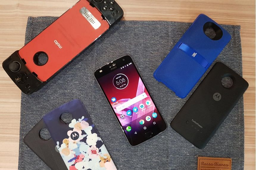 The new Moto Z2 Play (centre) will be available at telco M1 from July 29 and at Lenovo retailers and other telcos from Aug 5. The modular phone is backward compatible with previous Moto Mods and new ones released year, which include: (clockwise from