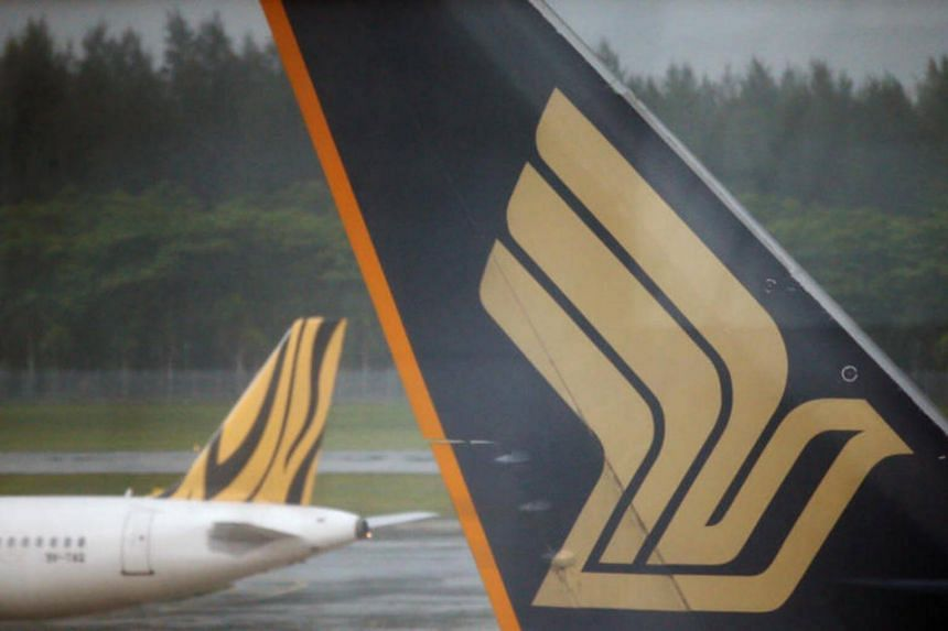 A Tiger Airways plane (left) passes a Singapore Airlines plane sitting on the tarmac at Changi Airport in Singapore.