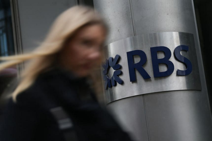 This file photo taken on Feb 25, 2017 shows a woman walking past a Royal Bank of Scotland (RBS) sign in central London.