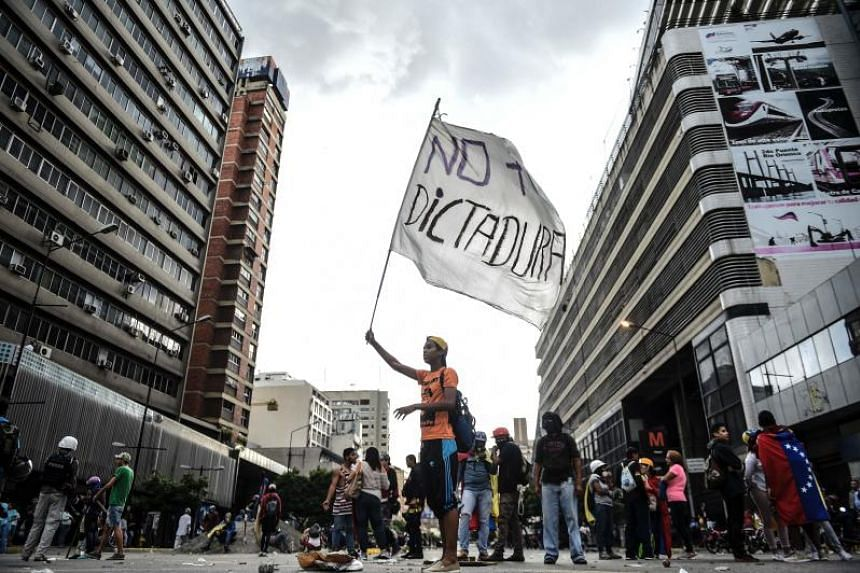 """An opposition activist hols a flag reading """"No more dictatorship"""" during a blockade to protest against Venezuelan President Nicolas Maduro in Caracas, on July 18, 2017."""