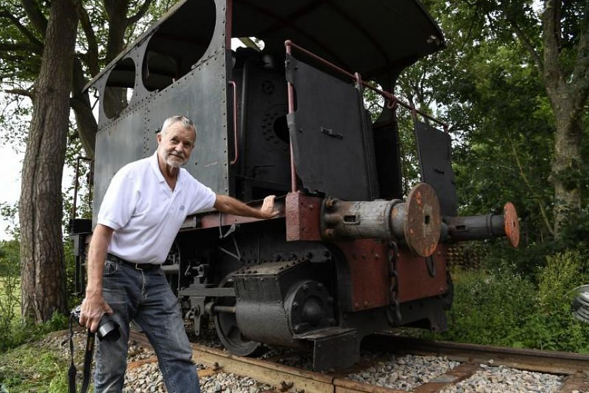 American Gregory Marshall poses next to a 1910 steam locomotive on July 11, 2017, at a old railway station in Dracy-Saint-Loup in central France.