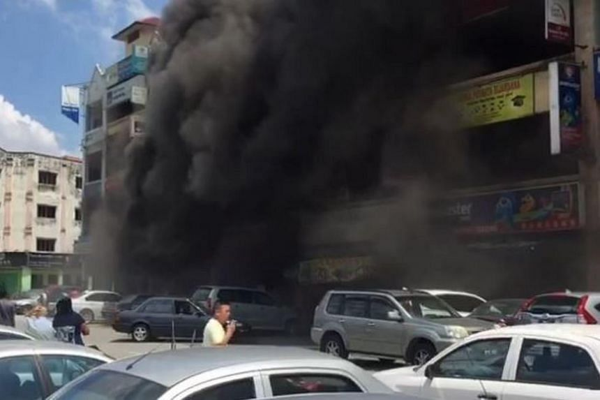Smoke billowing out from a motorcycle shop after a fire broke out, in Cheras, Kuala Lumpur, on July 27, 2017.