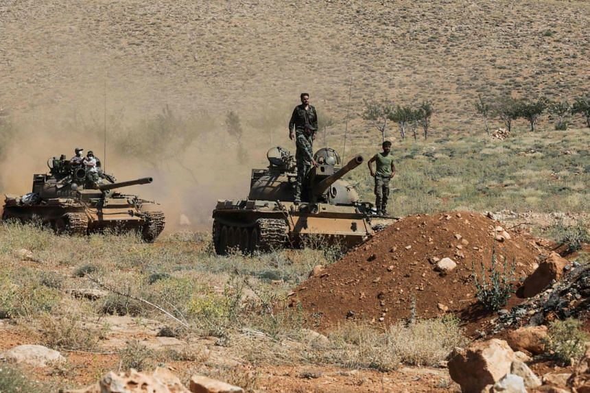 Syrian soldiers riding on a tank near Hezbollah fighters in a mountainous area around the Lebanese town of Arsal along the border with Syria.