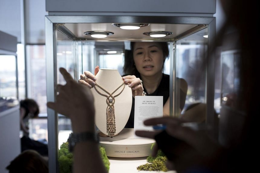 Marie Chiam, a marketing manager with Rio Tinto Diamonds, works on the installation of the company's showcase of diamonds and jewellery pieces.