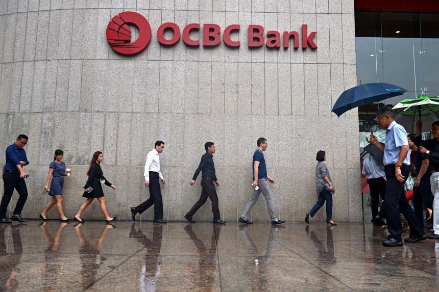 Office workers shelter themselves from the rain as they walk past the OCBC Bank Centre at Raffles Place.