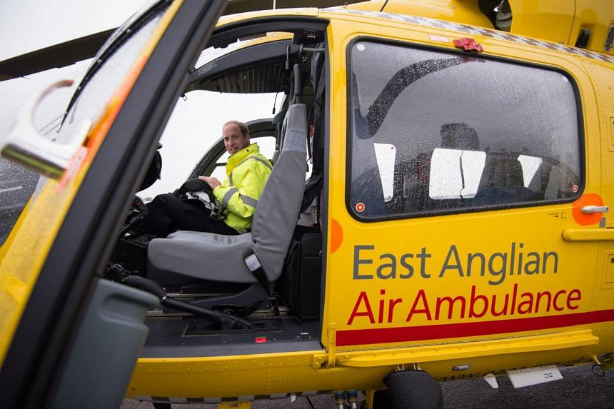 Britain's Prince William sits in the cockpit of his helicopter as he begins his new job as a co-pilot with the East Anglian Air Ambulance at Cambridge Airport in a 2015 photograph.