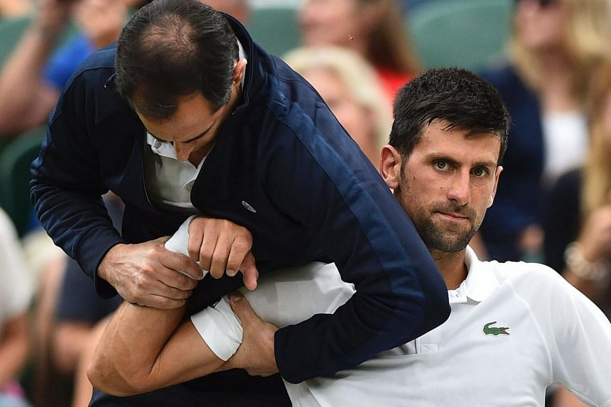 Novak Djokovic gets some medical attention on court in a break between games against France's Adrian Mannarino on July 11, 2017.