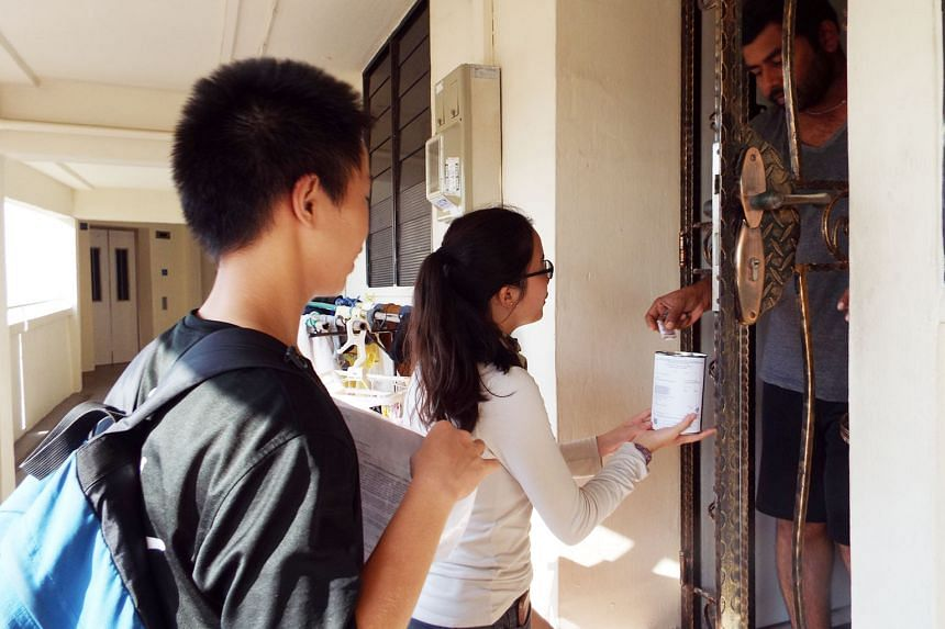 River Valley High School students Mao Yu Di, 16 (far left), and Lai Sin Yee, 17, appealing for donations from residents for their walkathon project.