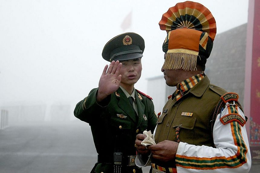 A Chinese soldier and an Indian soldier at a border crossing between the two countries.