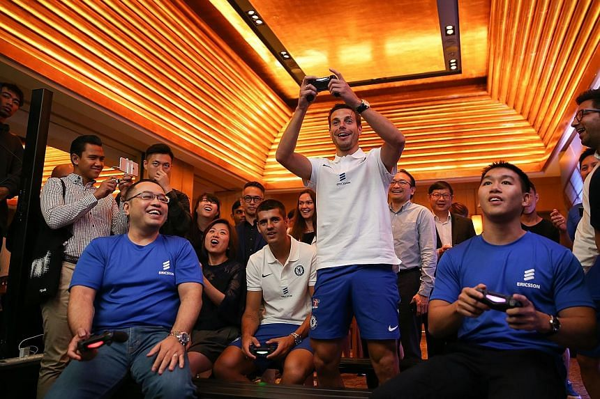 Chelsea striker Alvaro Morata and defender Cesar Azpilicueta (standing) playing Fifa at an event hosted by Ericsson yesterday. Morata will be the Blues' No. 1 choice up front this season.