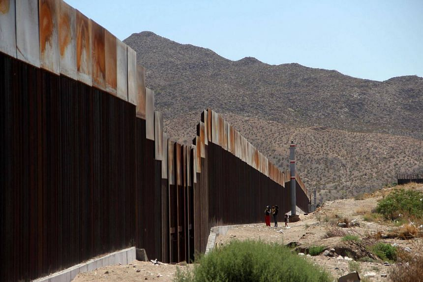 A Mexican family stands next to the border wall between Mexico and the United States, in Ciudad Juarez, Mexico on May 23, 2017.