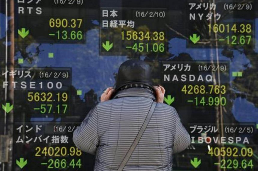 A pedestrian gazes at information of Tokyo's Nikkei Stock Average during an afternoon trade session and other global markets in Tokyo.