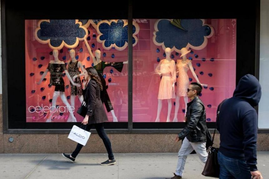 People walk past a store display in the window of Macy's flagship store on May 12, 2017.