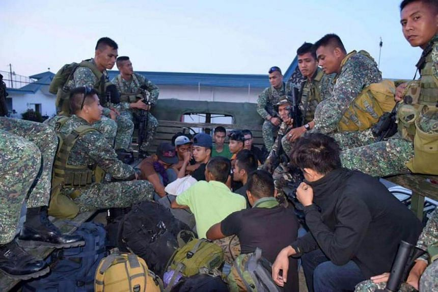 Philippine marines guarding suspects, arrested for trying to reinforce Muslim militants in Marawi, prior to their transportation to Manila.