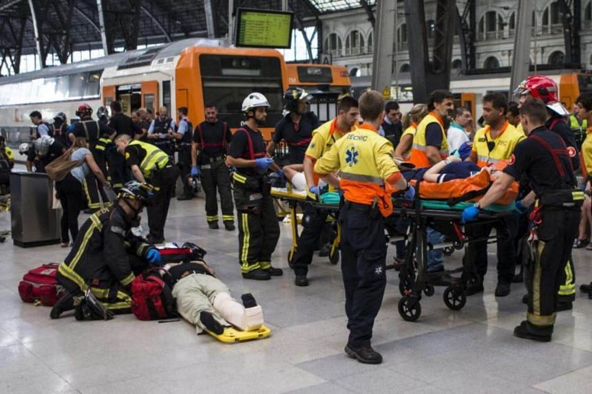 Spanish firefighters and paramedics treat injured people at Francia Railway Station in Barcelona, northeastern Spain on July 28, 2017.