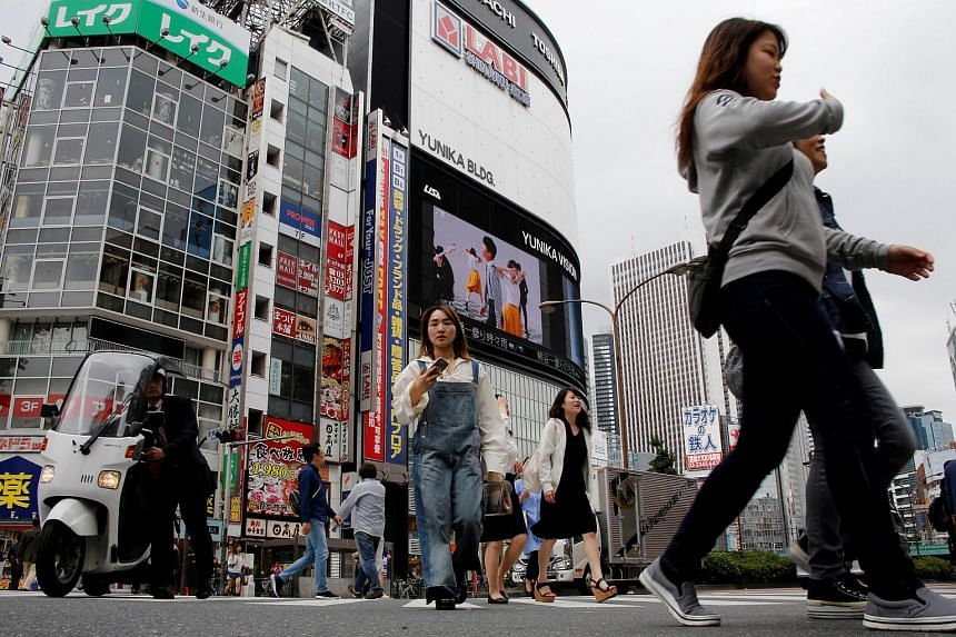 People cross a street in the Shinjuku shopping and business district in Tokyo.