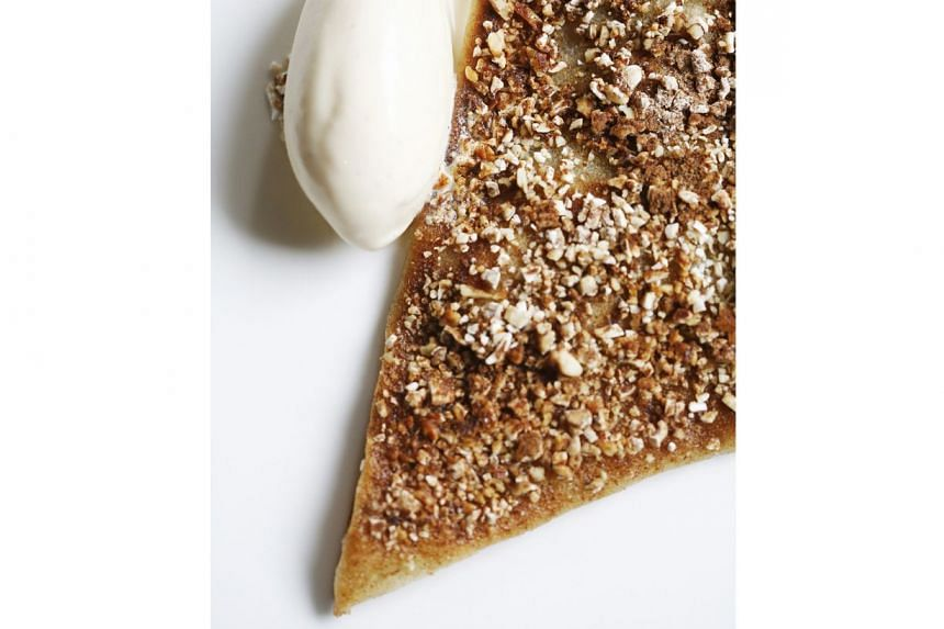 A fine apple tart a la dragee topped with chopped almonds and served with havana rum and raisin ice cream.