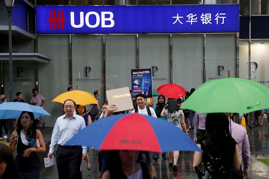Office workers carrying umbrellas pass a UOB bank branch in Singapore.