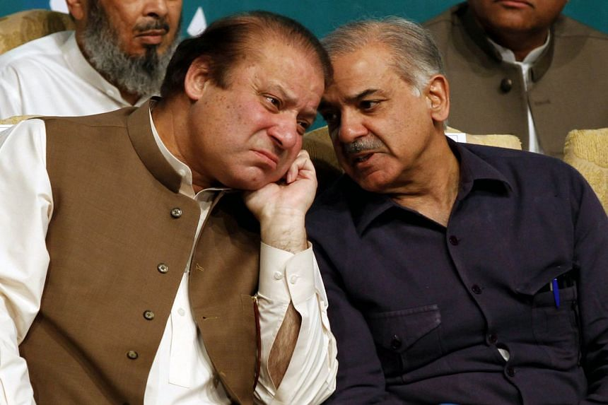 Nawaz Sharif (left) talks with his brother Shahbaz Sharif in a 2013 file photo.