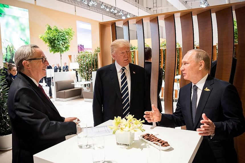 """From far left: European Commission president Jean-Claude Juncker, US President Donald Trump and Russian President Vladimir Putin in Hamburg, Germany, earlier this month. Mr Juncker said the new US sanctions could have """"unintended unilateral effects t"""
