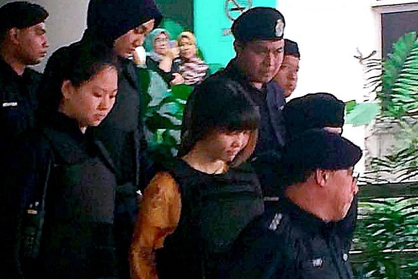 Indonesian Siti Aisyah (left) and Vietnamese Doan Thi Huong being escorted by police from the Shah Alam High Court in Selangor yesterday. Both women, who are charged with murdering Mr Kim Jong Nam on Feb 13, have said they believed they were taking p