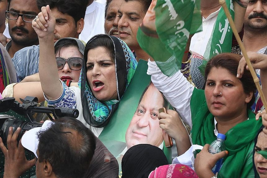 Supporters of Mr Nawaz Sharif, with one holding his picture, protesting in Lahore against the court verdict disqualifying him from holding the office of Prime Minister. Mr Sharif resigned soon after.