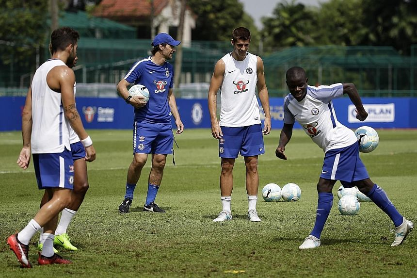 Chelsea midfielder Cesc Fabregas (far left) and Alvaro Morata look on as team-mate N'Golo Kante attempts to block a pass during a training session at the Singapore American School.