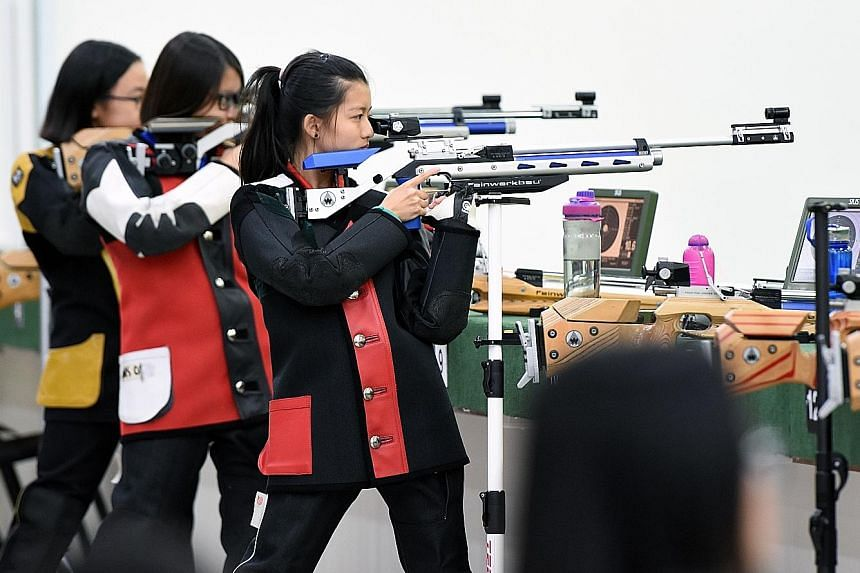 Above: Northbrooks Secondary's Gai Tianrui, 14, is the C Div boys' 10m air rifle winner. Left: Callie Siah (right) in action during the C Div girls' 10m air rifle final. She came from behind to win with 244.6 points.